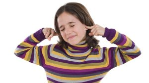 child with fingers in ears